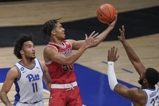 Northern Illinois' Anthony Crump (50) scores between Pittsburgh's John Hugley (23) and Justin Champagnie (11) during the first half of an NCAA college basketball game Saturday, Dec. 5, 2020, in Pittsburgh. (AP Photo/Keith Srakocic)