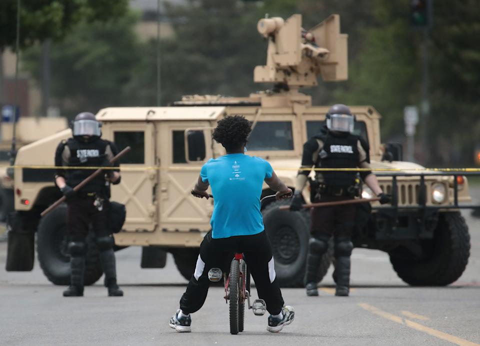 MINNEAPOLIS, MINNESOTA - MAY 29: A man rides a bicycle up to a law enforcement checkpoint after the city endured a night of protests and violence on May 29, 2020 in Minneapolis, Minnesota. The National Guard has been activated as protests continue after the death of George Floyd which has caused widespread destruction and fires across Minneapolis and St. Paul. (Photo by Scott Olson/Getty Images)
