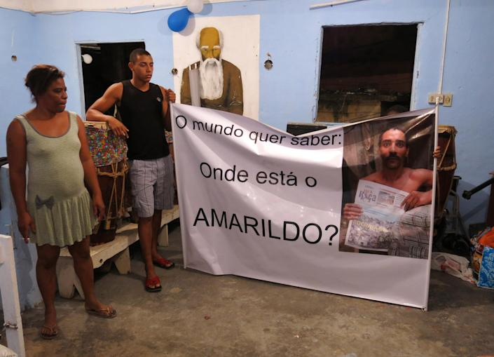 """In this Oct.1, 2013 photo, Amarildo de Souza's sister Maria Lacerda stands next to de Souza's son, Anderson, as he holds the end of a banner that reads in Portuguese; """"The world wants to know: where is Amarildo?,"""" at the Rocinha slum, in Rio de Janeiro, Brazil. De Souza, a bricklayer, disappeared in July after last being seen in police custody in Rocinha slum. This week, investigators said they've recommended to prosecutors that 10 police officers from the slum's """"pacifying"""" unit be charged with Amarildo's abduction, torture, death and disappearance. (AP Photo/Bradley Brooks)"""