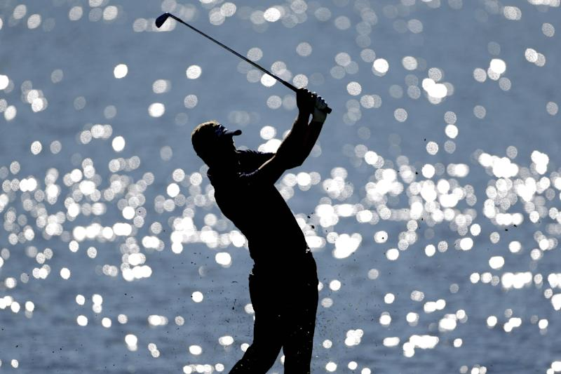 Luke Donald, of England, hits off the fairway on the 17th hole during the final round of the Tour Championship golf tournament, Sunday, Sept. 23, 2012, in Atlanta. (AP Photo/David Goldman)
