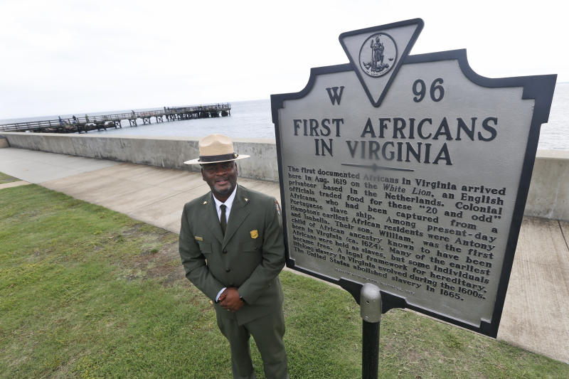 Terry E. Brown, Superintendent of the Fort Monroe National Monument poses next to a historical marker that signifies the spot of the first landing of Africans in America 400 years ago at Fort Monroe in Hampton, Va., Thursday, Aug. 15, 2019. (AP Photo/Steve Helber)