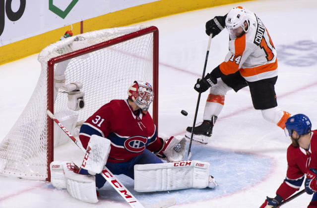 Philadelphia Flyers' Sean Couturier (14) shoots wide on Montreal Canadiens goaltender Carey Price during the second period of an NHL hockey game Thursday, Feb. 21, 2019, in Montreal. (Paul Chiasson/The Canadian Press via AP)