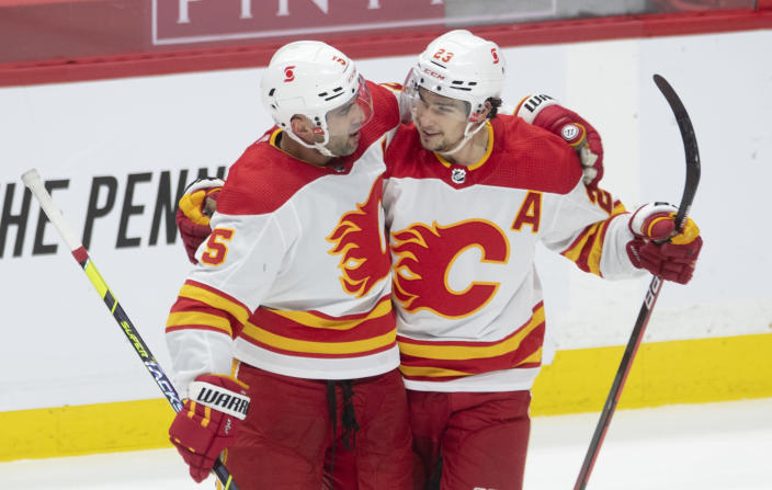 Calgary Flames center Sean Monahan, right, congratulates defenseman Mark Giordano on his goal during the second period on an NHL hockey game, Wednesday, March 24, 2021 in Ottawa, Ontario. (Adrian Wyld/The Canadian Press via AP)