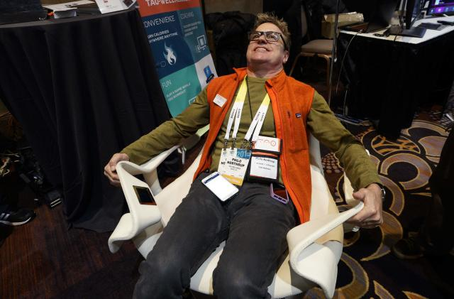 Philo Northrup, president of Tao Wellness, demonstrates the Tao Chair at the International Consumer Electronics show (CES) in Las Vegas, Nevada January 4, 2015. The chair allows a person to get an isometric workout using resistance against the chair while watching TV. REUTERS/Rick Wilking (UNITED STATES - Tags: BUSINESS SCIENCE TECHNOLOGY HEALTH)