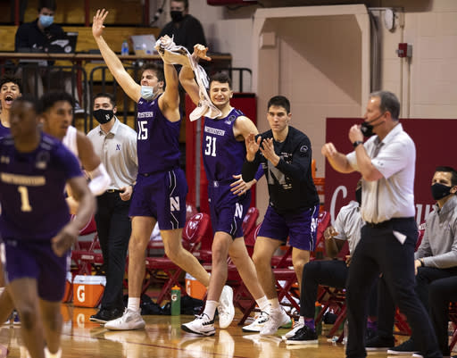 Players on Northwestern's bench react to a teammate's basket during the second half of an NCAA college basketball game against Indiana, Wednesday, Dec. 23, 2020, in Bloomington, Ind. (AP Photo/Doug McSchooler)