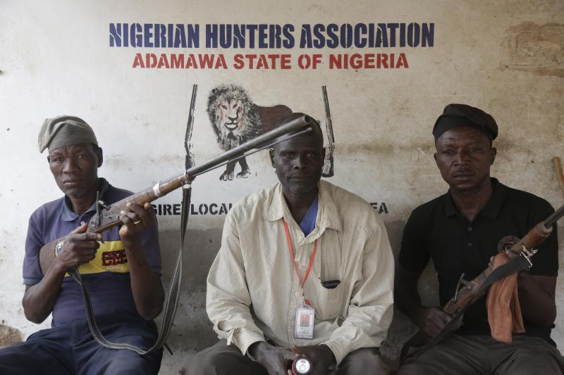 "Local hunters pose with dane guns near a polling station following the presidential election being delayed by the Independent National Electoral Commission in Yola, Nigeria, Saturday, Feb. 16, 2019. A civic group monitoring Nigeria's now-delayed election says the last-minute decision to postpone the vote a week until Feb. 23 ""has created needless tension and confusion in the country."" (AP Photo/Sunday Alamba)"