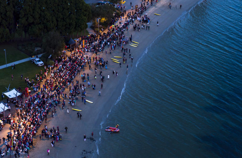 Participants of the Dark Mofo Nude Solstice Swim are seen gathered at the River Derwent at dawn, in Hobart, on June 22, 2018. (AAP Image/Rob Blakers)