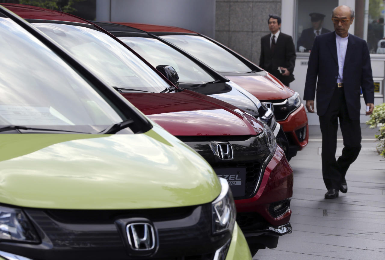 A man walks past Honda cars on display at Honda Motor Co. headquarters in Tokyo, Friday, April 28, 2017. Honda Motor Co. is reporting a 95.9 billion yen ($864 million) profit for January-March, a reversal from the 93.4 billion yen loss it racked up a year earlier, as the Japanese automaker recovers from costs for a massive air-bag recall. (AP Photo/Koji Sasahara)