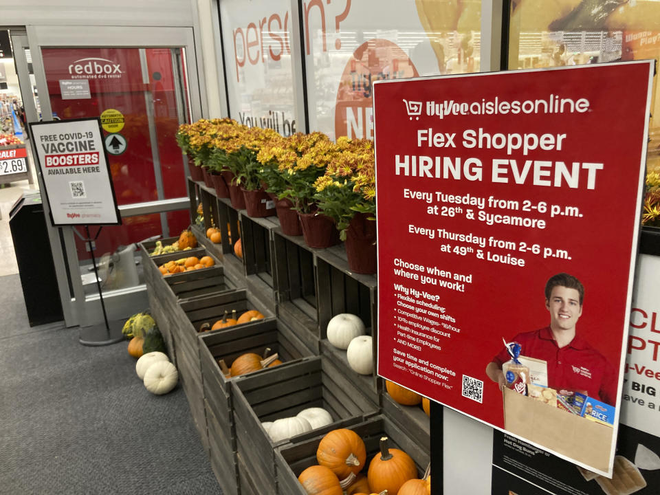 In this Thursday, Oct. 7, 2021, photograph, a sign advertising for workers stands outside a Hy-Vee grocery store in Sioux Falls, S.D. Companies that typically hire thousands of seasonal workers are heading into the holidays during one of the tightest job markets in decades, making it unlikely they'll find all the workers they need. For shoppers, it might mean a less than jolly holiday shopping experience, with bare store shelves and online orders that take longer than usual to fill. (AP Photo/David Zalubowski)