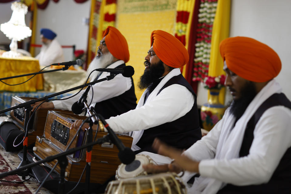 Musicians play Sikh hymns during Vaisakhi celebrations at Guru Nanak Darbar of Long Island, Tuesday, April 13, 2021 in Hicksville, N.Y. Sikhs across the United States are holding toned-down Vaisakhi celebrations this week, joining people of other faiths in observing major holidays cautiously this spring as COVID-19 keeps an uneven hold on the country. (AP Photo/Jason DeCrow)