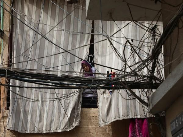 A woman is seen through electricity cables. (Photo Credit- Reuters)