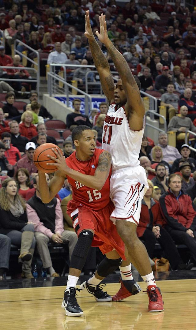 Hartford's Yolonzo Moore II, left, looks for help from the defense of Louisville's Chane Behanan during first half action of their NCAA mens college basketball game Nov. 19, 2013, in Louisville, Ky. (AP Photo/Timothy D. Easley)
