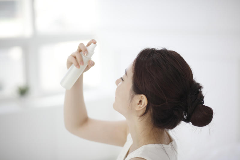 Young woman spraying mist on face