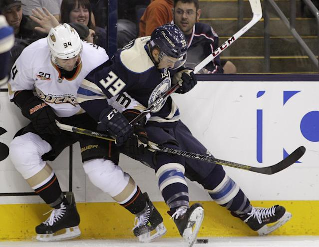Anaheim Ducks' Daniel Winnik, left, and Columbus Blue Jackets' Michael Chaput fight for a loose puck during the second period of an NHL hockey game Sunday, Oct. 27, 2013, in Columbus, Ohio. (AP Photo/Jay LaPrete)