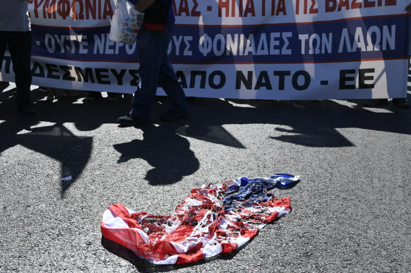 Protesters walk after burning a U.S. and a NATO flag during a demonstration against the visit of U.S. Secretary of State Mike Pompeo, in central Athens, Saturday, Oct. 5, 2019. Pompeo is in Greece on the last leg of a four-nation European tour that has been overshadowed by the impeachment inquiry in Washington.Pompeo has sought to avoid the drama back home by focusing on matters directly related to his trip. (AP Photo/Michael Varaklas)