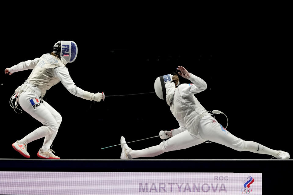 Marta Martyanova of the Russian Olympic Committee, right, and Astrid Guyard of France compete in the women's individual Foil team final medal competition at the 2020 Summer Olympics, Thursday, July 29, 2021, in Chiba, Japan. (AP Photo/Hassan Ammar)