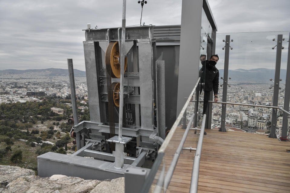 A man stands inside the new elevator at the Acropolis Archaeological site in Athens, Thursday, Dec 3, 2020. Acropolis became fully accessible for people with disabilities after a restoration of the pathways and the inauguration of a new elevator. (Louisa Gouliamaki/Pool via AP)