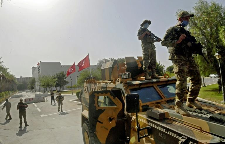 """Tunisian soldiers cordon off the parliament, which was suspended by President Kais Saied on Sunday, prompting allegations of a """"coup"""""""