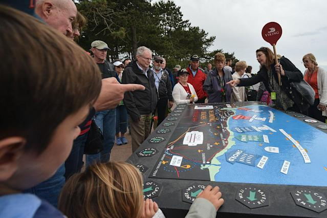 <p>A group of visitors look at the D-Day landing map located at the American Cemetery in Colleville-sur-Mer. (Photo: Artur Widak/NurPhoto via Getty Images) </p>