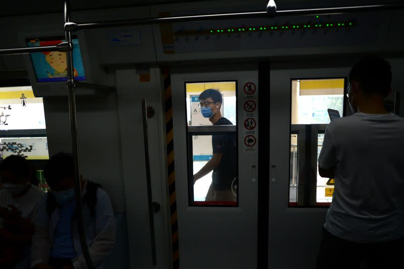 People wearing face masks commute inside a subway station during morning rush hour, following an outbreak of the novel coronavirus disease (COVID-19), in Beijing
