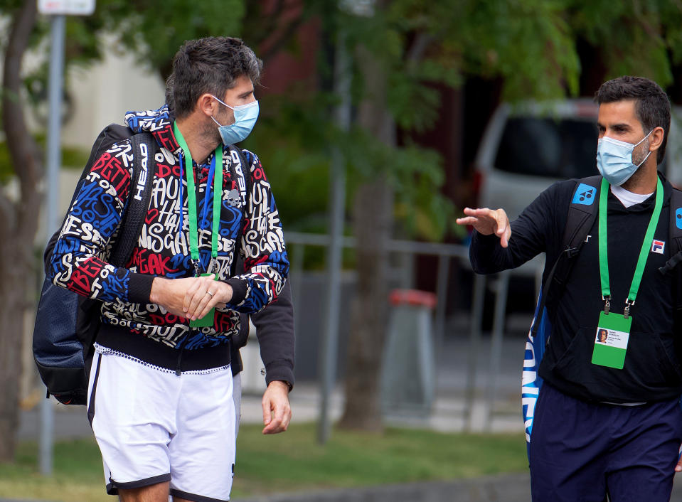 Italian tennis player Simone Bolelli, left, and Argentina's Maximo Gonzalez are escorted to their training session in Melbourne, Australia, Monday, Jan. 18, 2021. The number of players in hard quarantine swelled to 72 ahead of the Australian Open after a fifth positive coronavirus test was returned from the charter flights bringing players, coaches, officials and media to Melbourne for the season-opening tennis major. (Luis Ascui/AAP Image via AP)