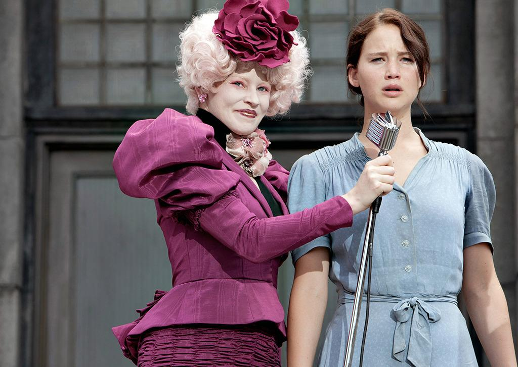 """<p>We are introduced to Effie (Elizabeth Banks) outfitted in a tailored fuchsia frock, pink wig with an oversized flower, and white pancake makeup as she enthusiastically accepts Katniss Everdeen (Jennifer Lawrence) as a Hunger Games tribute. """"She is a fashion victim,"""" costume designer Judianna Makovsky <a href=""""http://articles.latimes.com/2012/mar/18/image/la-ig-hunger-20120318"""">told the <i>Los Angeles Times</i></a>.</p>"""