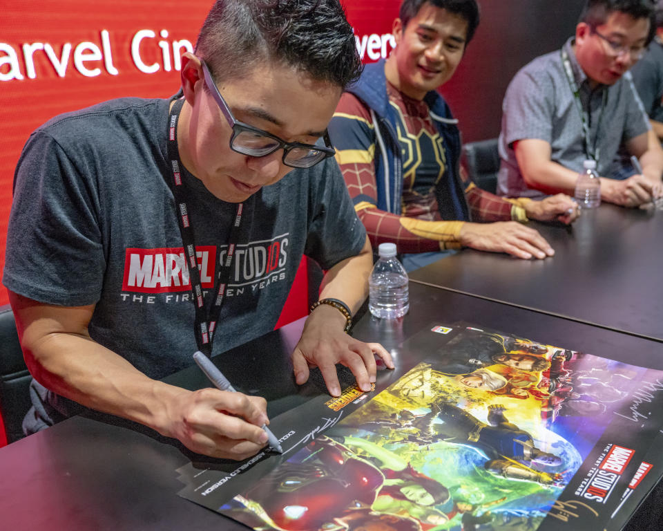 Andy Park, Supervisor of the Marvel Studios Visual Development Team signs Avengers: Infinity War posters at the Marvel Studios booth on day two of Comic-Con International on Friday, July 20, 2018 in San Diego, CA. (Photo by Christy Radecic/Invision/AP)