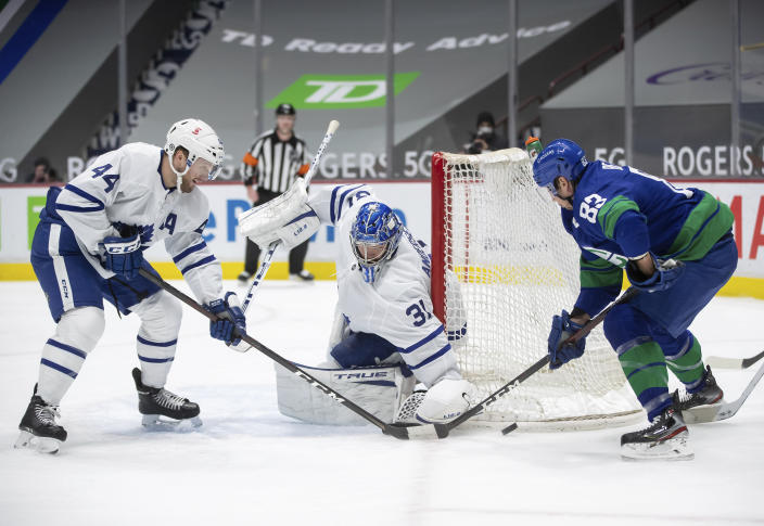 Toronto Maple Leafs goalie Frederik Andersen (31), of Denmark, stops Vancouver Canucks' Jay Beagle (83) as Toronto's Morgan Rielly (44) defends during the second period of an NHL hockey game in Vancouver, British Columbia, on Saturday, March 6, 2021. (Darryl Dyck/The Canadian Press via AP)