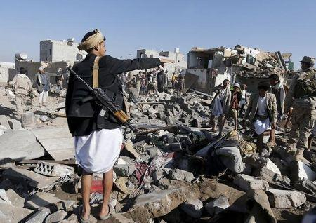 An armed man gestures as he stands on the rubble of houses destroyed by an air strike near Sanaa Airport March 26, 2015. REUTERS/Khaled Abdullah