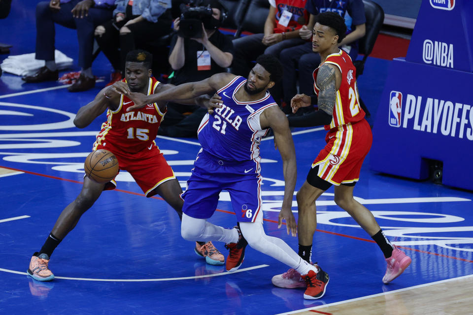 PHILADELPHIA, PENNSYLVANIA - JUNE 16: Clint Capela #15 of the Atlanta Hawks and Joel Embiid #21 of the Philadelphia 76ers reach for the ball during the third quarter during Game Five of the Eastern Conference Semifinals at Wells Fargo Center on June 16, 2021 in Philadelphia, Pennsylvania. NOTE TO USER: User expressly acknowledges and agrees that, by downloading and or using this photograph, User is consenting to the terms and conditions of the Getty Images License Agreement. (Photo by Tim Nwachukwu/Getty Images)