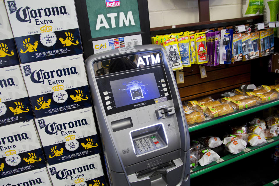 FILE - In this April 18, 2018, file photo, an ATM machine is in use at a New York convenience store. If you find yourself short on cash while on vacation, it might seem easiest to hit up the nearest ATM. But if that handy machine is not in your bank's network, you could get a double whammy of fees: The ATM owner will probably charge a few dollars for the convenience, and your own bank may tack on an extra $2.50 or so. (AP Photo/Mark Lennihan, File)