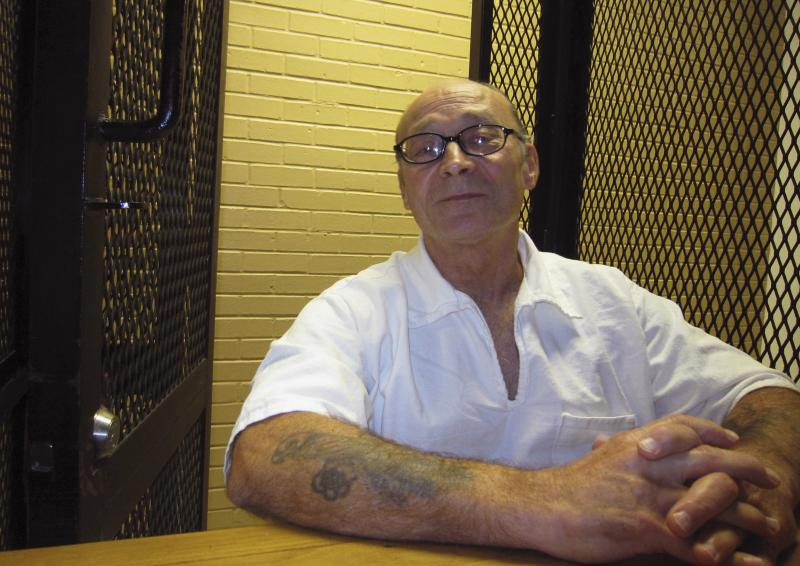 Inmate Arnold Darby speaks during an interview in a holding area at the Goree Unit prison in Huntsville, Texas December 5, 2013. Darby was once one of the most prodigious bootmakers in the Texas prison system, turning out more than 1,000 pairs for lawman, FBI agents and the governor's office. After 37 years behind bars, serving time for robbery and murder, Darby was released on parole in 2011. After only a year on the outside, Darby violated parole by driving while intoxicated and was sent back to prison. This time, however, he has not been in the new unit long enough to earn what is considered a privileged position in a workshop, and the once-vaunted jailhouse cobbler is not sure if he will ever make boots again. Picture taken December 5, 2013. TO MATCH FEATURE USA-PRISONER/BOOTS REUTERS/Jon Herskovitz (UNITED STATES - Tags: CRIME LAW)