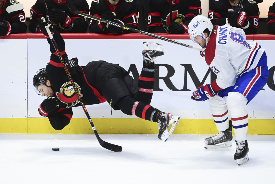 Ottawa Senators right wing Connor Brown (28) gets hit to the ice by Montreal Canadiens defenseman Ben Chiarot (8) during the third period of an NHL game in Ottawa, Ontario on Tuesday, Feb. 23, 2021. (Sean Kilpatrick/The Canadian Press via AP)