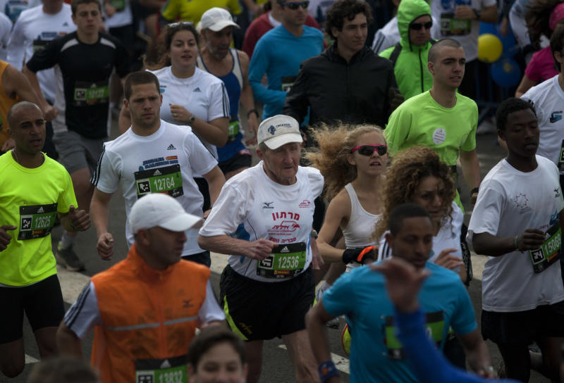 77-year-old Holocaust survivor Hanoch Shahar, center, runs in Jerusalem, Friday, March 16, 2012. About 15,000 runners, including 1,500 from overseas, are competing Friday, with some 1,000 competitors expecting to complete the full 42 kilometers (26.2 miles) marathon distance, with others aiming to complete shorter distances, including Mayor Nir Barkat who says he plans to run half a marathon and 77-year old Hanoch Shahar aiming for 10Km. (AP Photo/Sebastian Scheiner)