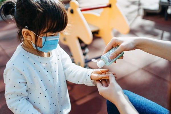 Young mother squeezing hand sanitizer onto little daughter's hand in the playground to prevent the spread of viruses -