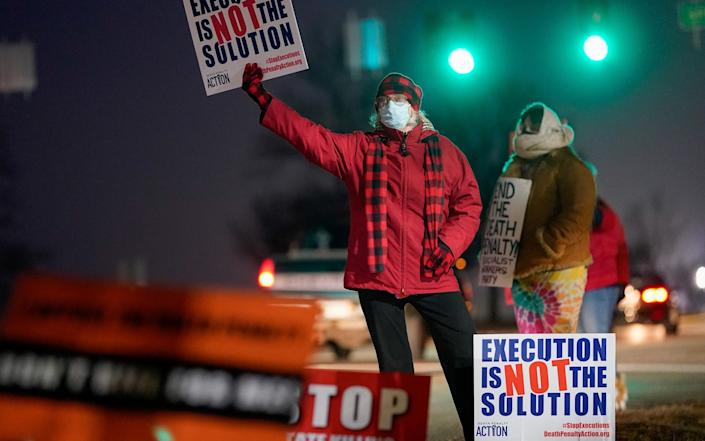 Activists in opposition to the death penalty gather to protest the execution of Lisa Montgomery - Bryan Woolston/Reuters