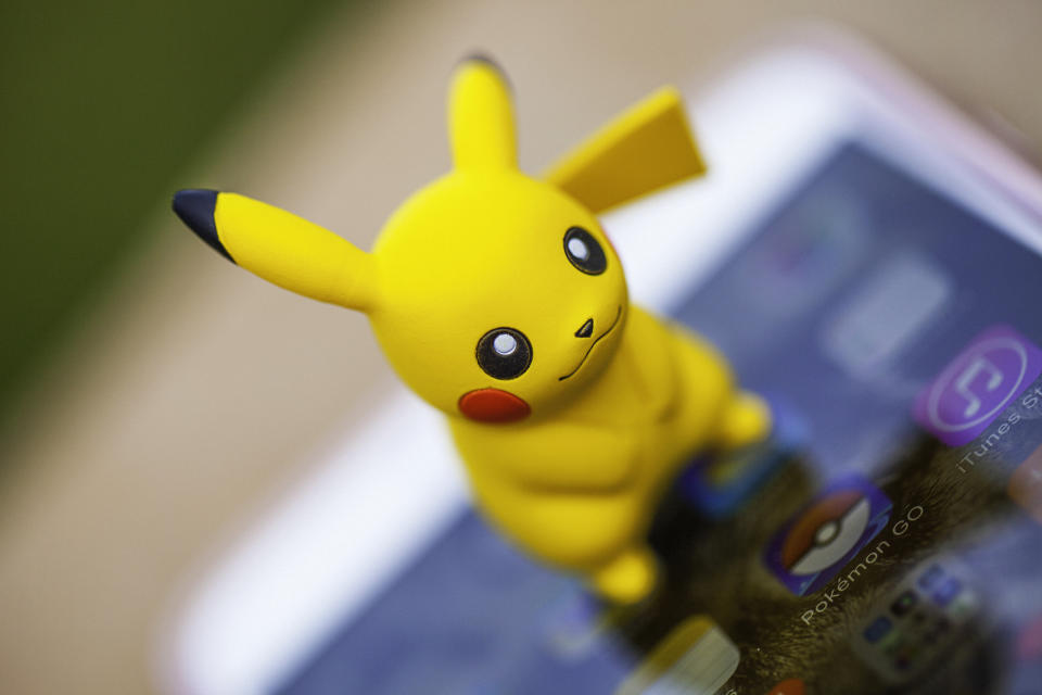 Peyton, Colorado, USA - August 17, 2016: A horizontal shot of the Pokemon Go character Pikachu, standing on top of an Apple iPhone 6 Plus. The Pokemon Go icon can be seen on the phone screen. The character and phone are on a wall outdoors, in front of a defocused grassy area in Peyton, Colorado. The figurine is made by Tomy.