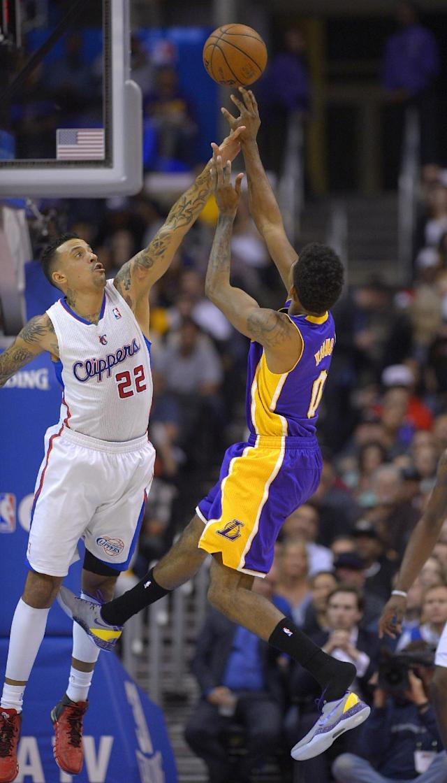 Los Angeles Lakers forward Nick Young, right, loses his shoe as he puts up a shot while Los Angeles Clippers forward Matt Barnes defends during the first half of an NBA basketball game, Friday, Jan. 10, 2014, in Los Angeles. (AP Photo/Mark J. Terrill)