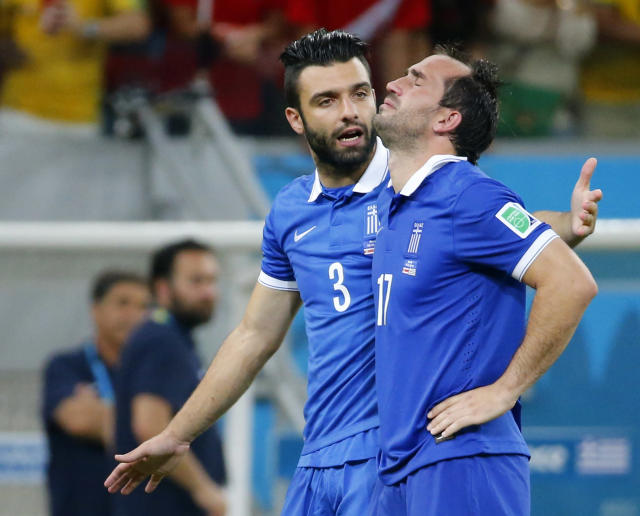 Greece's Theofanis Gekas (R) is comforted by his teammate Giorgios Tzavellas after losing their penalty shootout to Costa Rica in their 2014 World Cup round of 16 game at the Pernambuco arena in Recife June 29, 2014. Gekas missed his decisive shot. REUTERS/Yves Herman (BRAZIL - Tags: SOCCER SPORT WORLD CUP TPX IMAGES OF THE DAY)