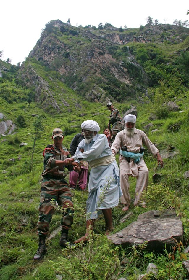 Indian army officials help travellers and villagers down a steep slope after they were stranded by the rising floodwaters of the River Alaknanda near Govindghat, Chamoli District in the northern Indian state of Uttarakhand on June 18, 2013. Military helicopters have carried out emergency food drops June 19, for thousands of people stranded by flash flooding from early monsoon rains which has killed at least 120 in northern India, officials said. AFP PHOTO/STR