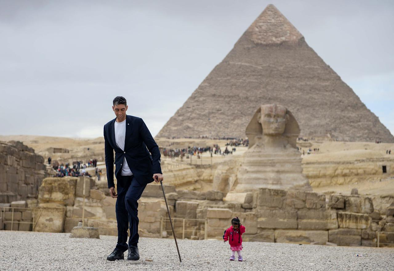 <p>Turkey's Sultan Kosen, the world's tallest man, left, poses with Jyoti Amge of India, the world's shortest woman at the site of the Pyramids of Giza in Egypt on Jan. 26, 2018, with the Sphinx and the Pyramid of Khafre — also known as Chephren — seen in the background. Photo from STRINGER/AFP/Getty Images. </p>