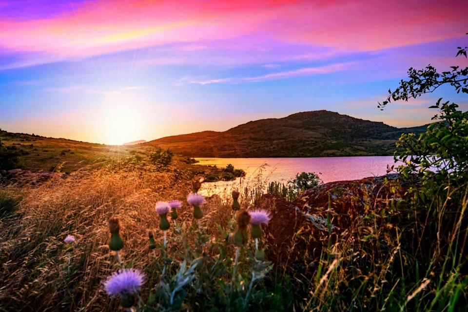greens plants and a lake below the Wichita Mountains in Lawton, Oklahoma at sunset