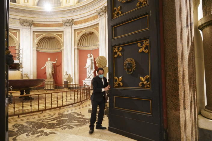 """Gianni Crea, the Vatican Museums chief """"Clavigero"""" key-keeper, opens the door of the 16th century """"Pio Clementino"""" section, the museum's oldest one, at the Vatican, Monday, Feb. 1, 2021. Crea is the """"clavigero"""" of the Vatican Museums, the chief key-keeper whose job begins each morning at 5 a.m., opening the doors and turning on the lights through 7 kilometers of one of the world's greatest collections of art and antiquities. The Associated Press followed Crea on his rounds the first day the museum reopened to the public, joining him in the underground """"bunker"""" where the 2,797 keys to the Vatican treasures are kept in wall safes overnight. (AP Photo/Andrew Medichini)"""