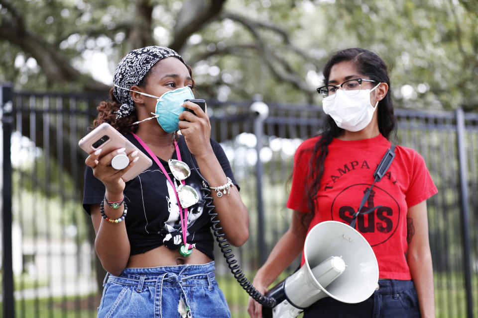 TAMPA, FL - JULY 02: University of South Florida students Makyla Burks, (L) and Eithne Silva both wear face masks while protesting in front of the Lifsey residence where the USF President Steven Currall lives on campus on July 2, 2020 in Tampa, Florida. Tampa Bay Students for Democratic Society protest at the University of South Florida demanding an increase in Black student enrollment, employ more Black faculty and staff, more financial aid, and make direct connections with the surrounding community. (Photo by Octavio Jones/Getty Images)
