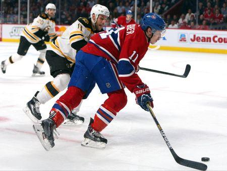 May 12, 2014; Montreal, Quebec, CAN; Montreal Canadiens right wing Brendan Gallagher (11) plays the puck against Boston Bruins center Gregory Campbell (11) during the third period in the game six of the second round of the 2014 Stanley Cup Playoffs at Bell Centre. Mandatory Credit: Jean-Yves Ahern-USA TODAY Sports