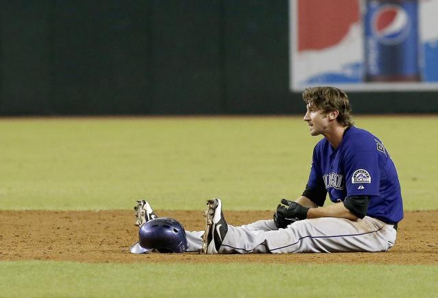 Colorado Rockies' Charlie Blackmon sits on the ground after being caught off second base in the sixth inning of a baseball game against the Arizona Diamondbacks on Friday, Sept. 13, 2013, in Phoenix. (AP Photo/Ross D. Franklin)