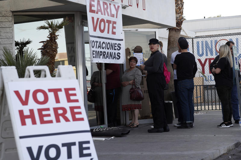 FILE - In this Feb. 15, 2020, file photo, people wait in line at an early voting location at the culinary workers union hall in Las Vegas. The Democratic presidential contest has moved to immigrant-heavy Nevada, but the issues of immigration are seldom getting a thorough airing on the campaign trail. Candidates usually throw in a quick condemnation of President Donald Trump's hard-line policies but have shied away from outlining their own immigration positions. Immigration groups say that points to a potential vulnerability for whoever is the Democratic nominee later this year. (AP Photo/John Locher, File)
