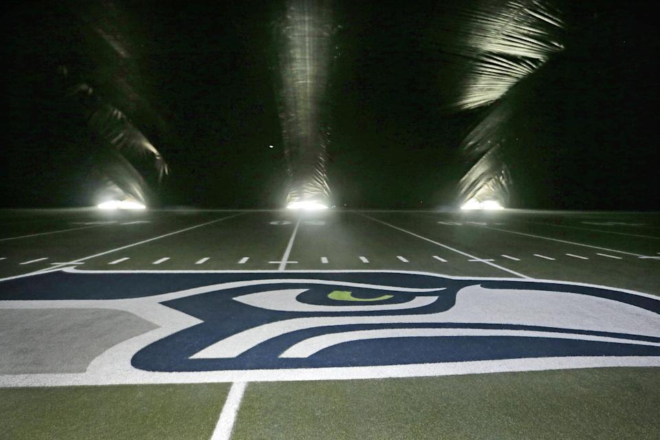 A newly-painted Seattle Seahawks' logo for the divisional playoff game sits in the center of the field in the dark under a giant tarp covering the artificial playing surface at the teams' field, CenturyLink Field, Thursday, Jan. 8, 2015, in preparation for Saturday's game against the Carolina Panthers, in Seattle. The tarp, resembling a massive pillow as fans blowing from underneath lift it up to several stories high, is protecting and allowing newly-painted logos and field markings underneath to dry. (AP Photo/Elaine Thompson)