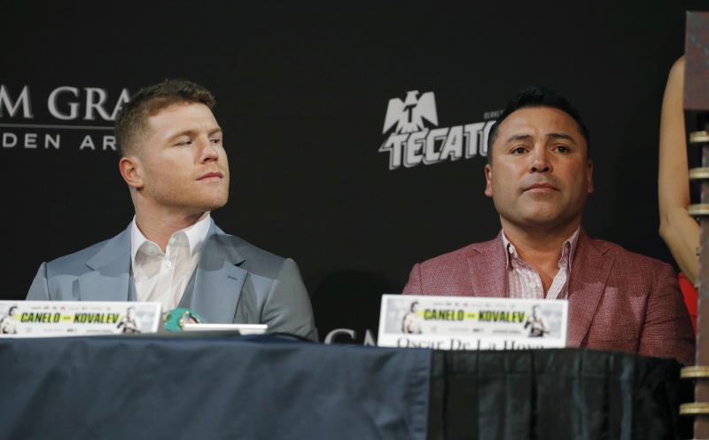 Canelo Alvarez, left, looks at promoter and former boxer Oscar de la Hoya during a news conference Wednesday, Oct. 30, 2019, in Las Vegas. Alvarez is scheduled to fight Sergey Kovalev in a WBO light heavyweight title bout Saturday in Las Vegas. (AP Photo/John Locher)