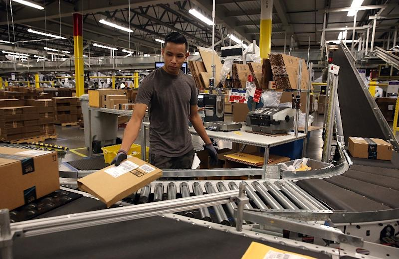 This file photo taken on January 19, 2015 shows an Amazon.com worker sorting packages onto a conveyor belt at an Amazon facility in Tracy, California (AFP Photo/JUSTIN SULLIVAN)